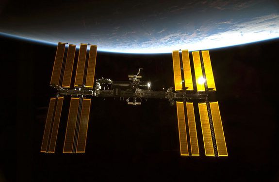 A company called Made in Space wants to use 3-D printers to make parts for spacecraft and space stations in orbit. In this photo, taken in February 2010, sunlight glints off the International Space Station, with the blue limb of Earth providing a dramatic backdrop.