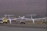 SpaceShipOne, with pilot Brian Binnie at the controls, rolls onto the runway tucked under its White Knight mothership during its second Anasari X Prize flight attempt on Oct. 4, 2004.