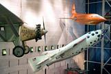 SpaceShipOne, the first privately built and piloted vehicle to reach space, hangs between Charles Lindbergh's Spirit of St. Louis, left, and Chuck Yeager's Bell X-1, above right, in the Milestones of Flight in the National Air and Space Museum's building on the National Mall in Washington, D.C.