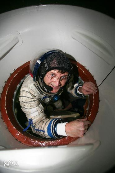 American entrepreneur Charles Simonyi peers out of the hatch of a Russian Soyuz spacecraft simulator during prelaunch training for his 13-day flight to the International Space Station.