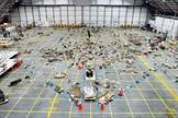 An overview of the Columbia debris reconstruction hangar in 2003 shows the orbiter outline on the floor with some of the 78,760 pieces identified to that date. More than 84,000 pieces of shuttle debris were recovered, some of which is included in a traveling NASA display to stress safety.