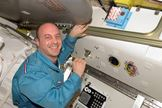 Astronaut Garrett Reisman, Expedition 16/17 flight engineer, poses for a photo after signing the Expedition 16 patch, which was added to the growing collection of insignias representing crews who performed spacewalks from the Quest Airlock of the ISS.