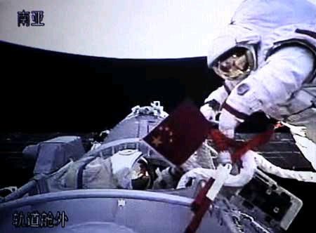 Zhai Zhigang waves the flag of the People's Republic of China from space, as his crewmate, Liu Boming, peeks his head out of the hatch.