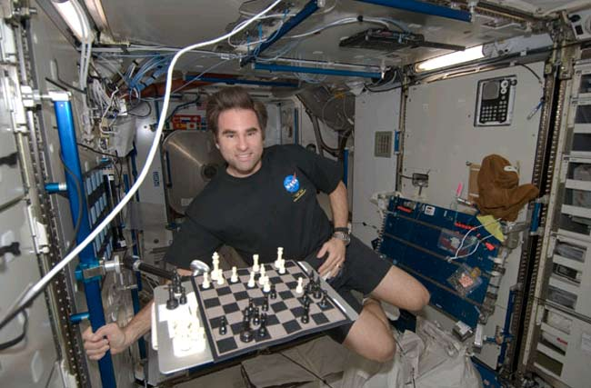 NASA astronaut Greg Chamitoff, Expedition 17 flight engineer, smiles for a photo near a chess board in the Harmony node of the International Space Station, July 19, 2008. Credit: NASA