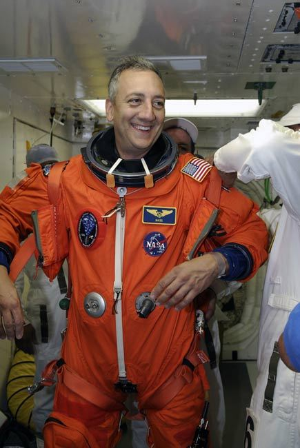 STS-125 Mission Specialist Mike Massimino s helped by a suit technician to don a harness over his launch and entry suit before entering space shuttle Atlantis for a simulated launch countdown.