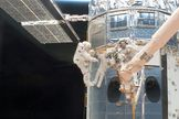 What appears to be a number of astronauts, because of the shiny mirror-like surface of the temporarily-captured Hubble Space Telescope, is actually only two - astronauts John Grunsfeld (left) and Andew Feustel during a May 14, 2009 spacewalk, the first of five during their STS-125 mission.