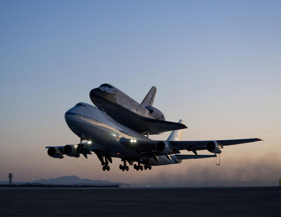 Space shuttle Discovery and its modified 747 carrier aircraft lift off from Edwards Air Force Base early in the morning of Sept. 20, 2009 on the first leg of its ferry flight back to the Kennedy Space Center in Florida.