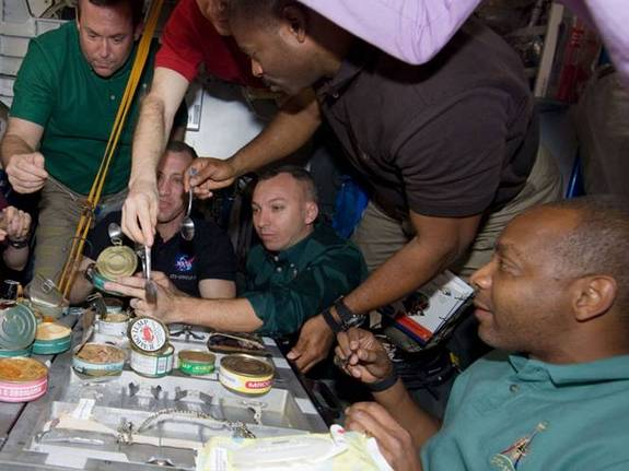 Members of the STS-129 crew share a meal while on the space station. The scene on Thanksgiving day will be similar onboard space shuttle Atlantis.