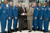 The STS-129 astronaut crew presents the space-flown flip coin to NFL officials at the Pro Football Hall of Fame on Jan. 27, 2010. The coin will decide the start of Super Bowl 44 in South Florida.