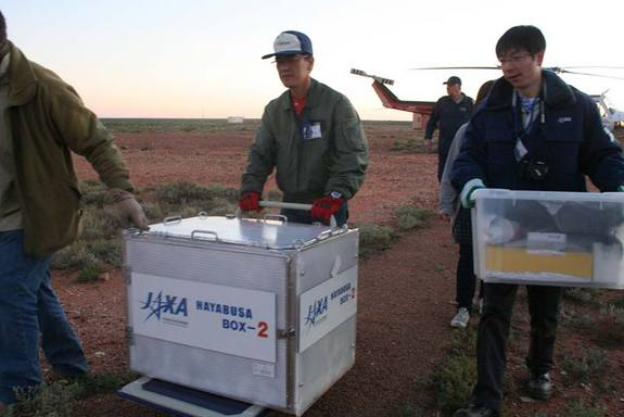 The sample return capsule (inside a box) from Japan's Hayabusa asteroid probe is transported by helicopter to the Instrumentation Building inside the Woomera Test Range after its June 13, 2010 landing. The re-entry capsule was housed in a temporary clean room before being returned to Japan on Tuesday. <a href=http://www.space.com/missionlaunches/japan-hayabusa-asteroid-probe-return-100614.html>Full Story</a>.