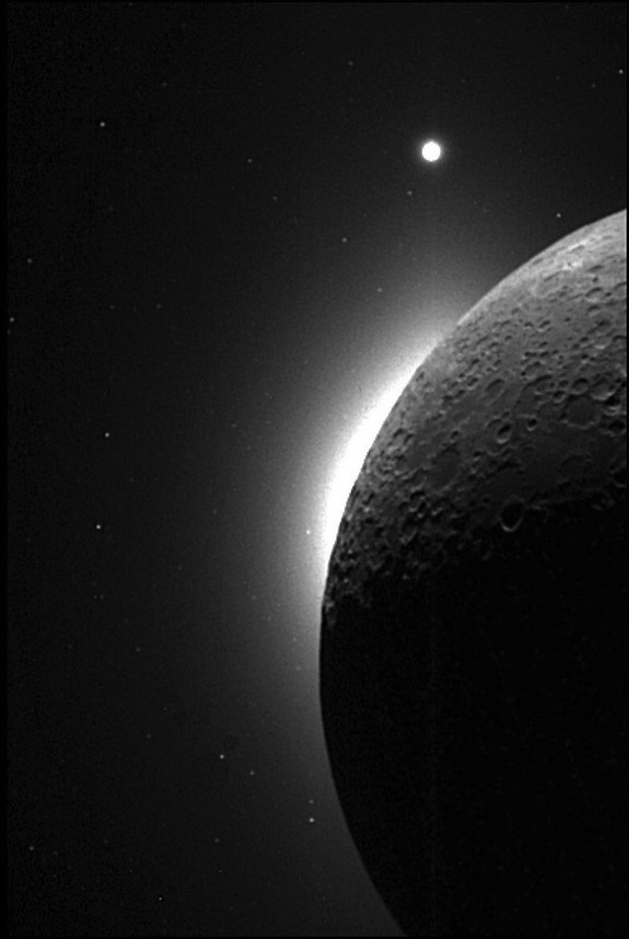 The slim, bright crescent, known as the Lunar Horizon Glow (LHG) was glimpsed several times during Apollo missions. This picture was taken with the Clementine spacecraft, when the sun was behind the moon. The white area on the edge of the moon is the LHG, and the bright dot at the top is the planet Venus.