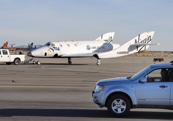 SpaceShipTwo is towed back to the hangar Jan. 13, 2011 under the watchful eye of East Kern Airport District Security Chief Mike Sterbens after a successful drop test and landing at the Mojave Air and Space Port in California.