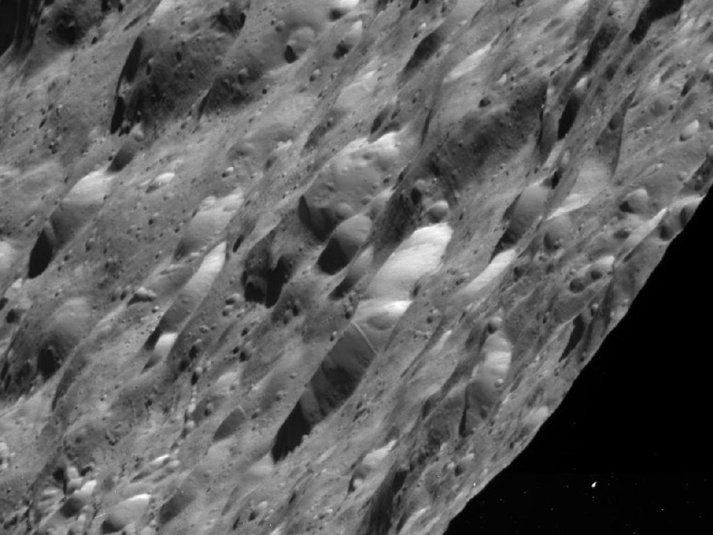 New Photos of Saturn Moon Show a Pockmarked Place