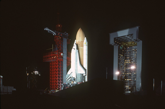 A nighttime view of the space shuttle Enterprise, mated to an external tank and solid rocket boosters, resting on the launch mount next to the access tower at Space Launch Complex Six.
