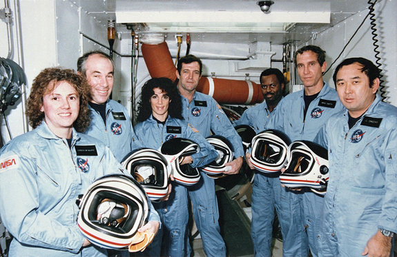 "On Jan. 28, 1986, NASA faced its first shuttle disaster, the loss of the Challenger orbiter and its seven-astronaut crew. Here, Challenger's last crew – members of the STS-51L mission – stand in the White Room at Pad 39B following the end of a launch dress rehearsal. They are (L to R) Teacher in Space Participant, Sharon ""Christa"" McAuliffe, Payload Specialist, Gregory Jarvis, Mission Specialist, Judy Resnik, Commander Dick Scobee. Mission Specialist, Ronald McNair, Pilot, Michael Smith and Mission Specialist, Ellison Onizuka."