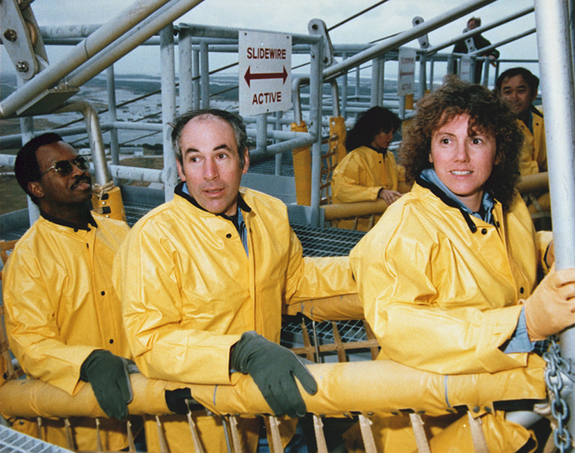The STS-51L Challenger flight crew receives emergency egress training in the slide wire baskets. They are (L to R) Mission Specialist, Ronald McNair, Payload Specialist, Gregory Jarvis, Teacher in Space Participant, Christa McAuliffe. Directly behind them are Mission Specialist Judy Resnik and Mission Specialist, Ellison Onizuka.