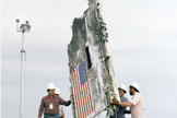 Workers lower STS-51L Challenger wreckage remains and boxes of debris into abandoned Minuteman Missile Silos at Complex 31 on Cape Canaveral Air Force Station.