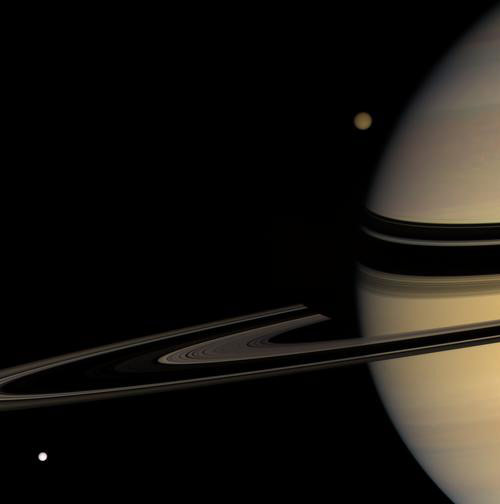 Titan emerges from behind Saturn while Tethys streaks into view in this colorful scene on March 24, 2008. Titan is 5,150 kilometers (3,200 miles) wide; Tethys is 1,071 kilometers (665 miles) wide. Saturn's shadow darkens the far arm of the rings near the