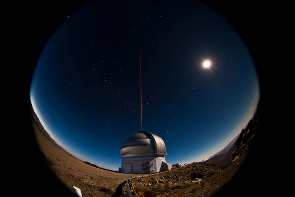 The Gemini South telescope on the night of January 21-22, 2011 during the first propagation of the GeMS laser guide star system on the sky. A bright gibbous moon illuminates the landscape for this 20-second fisheye lens view.