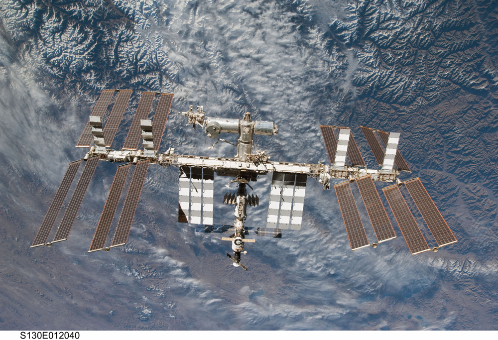 Backdropped by rugged Earth terrain, the International Space Station is featured in this image photographed by an STS-130 crew member on space shuttle Endeavour after the station and shuttle began their post-undocking relative separation.
