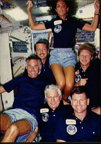 Discovery's first crew, the astronauts of STS 41-D, pose in the middeck for an onboard crew portrait during the shuttle's first flight in 1984.