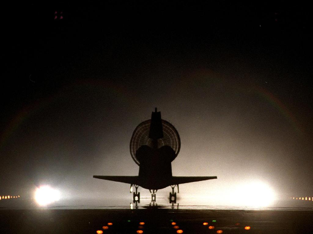 With its drag chute fully deployed, space shuttle Discovery lands on Kennedy's brightly lighted Shuttle Landing Facility runway 15, completing the 9-day, 19-hour, 13-minute and 1-second STS-96 mission. Main gear touchdown was at 2:02:43 a.m. EDT June 6, l