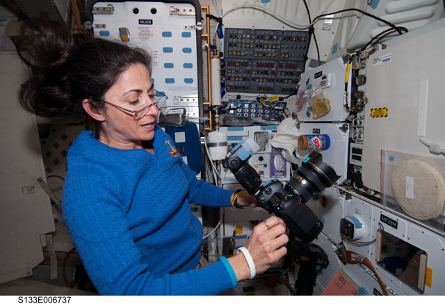 Astronaut Nicole Stott wearing glasses aboard Discovery on STS-133
