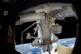 Discovery STS-133 astronaut Steve Bowen stands at the tip of the International Space Station's Canadian robotic arm, with the Earth and space shuttle in the background, during the second spacewalk of his mission on March 2, 2011.