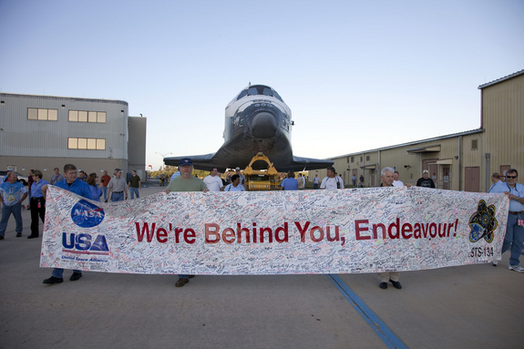At NASA's Kennedy Space Center in Florida, employees hold up a banner to commemorate space shuttle Endeavour's STS-134 mission as it is moved from its hangar to the Vehicle Assembly Building on Feb. 28, 2011. The shuttle is due to launch its final mission STS-134 on April 19, 2011.