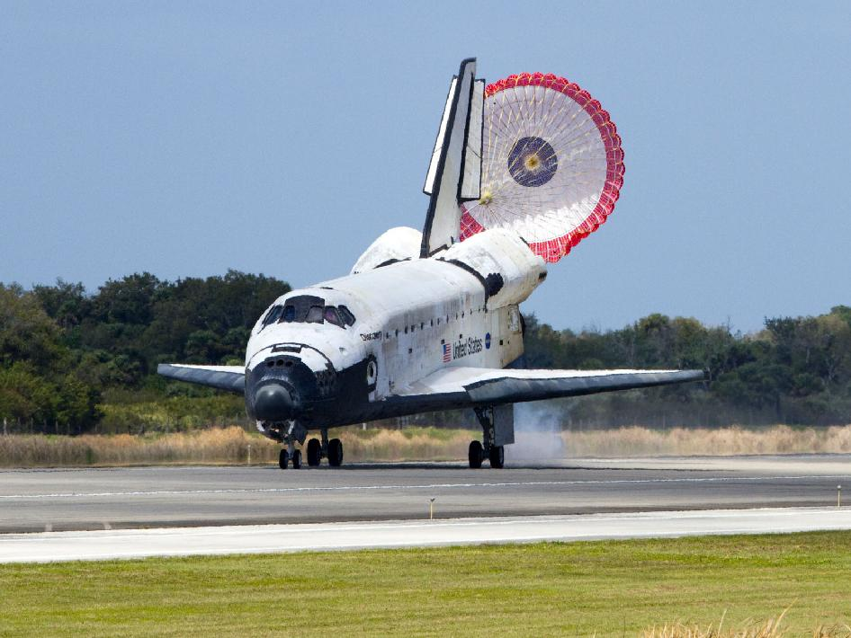 With its drag chute unfurled, space shuttle Discovery rolls down Runway 15 at the Shuttle Landing Facility at NASA's Kennedy Space Center in Florida. Landing was at 11:57 a.m. EST, completing the 13-day STS-133 mission to the International Space Station.