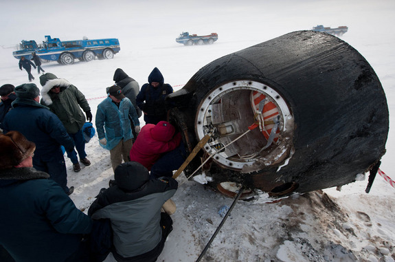 Russian support personnel work to help get crew members out of the Soyuz TMA-01M spacecraft shortly after the capsule landed with Expedition 26 Commander Scott Kelly and Flight Engineers Oleg Skripochka and Alexander Kaleri near the town of Arkalyk, Kazakhstan on Wednesday, March 16, 2011.