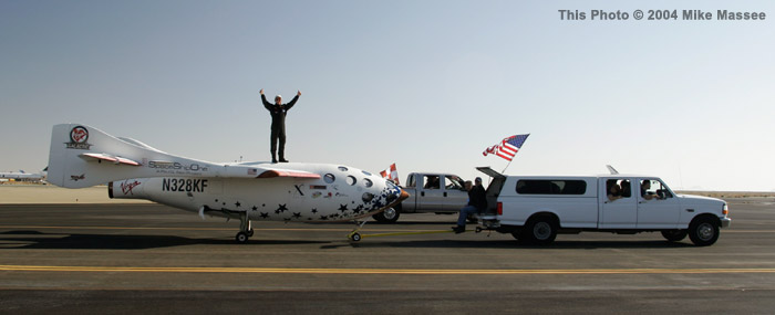 Pilot Mike Melvill has some fun celebrating his successful private suborbital flight atop SpaceShipOne, as the tow vehicle pulls it to the general viewing area.