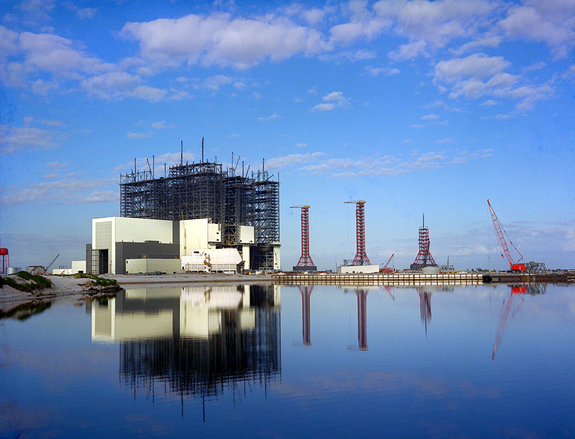 The Vehicle Assembly Building (VAB) undergoes construction in early 1965 at Kennedy Space Center, with the Launch Control Center (LCC) and Service Towers viewed from across the Turning Basin. The largest one-story building in the world, it housed Saturn V rocket assembly activities, later converted to space shuttle procedures.