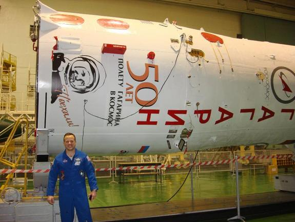 "NASA astronaut Ron Garan poses in front of the booster for the ""Yuri Gagarin"" Soyuz spacecraft that will carry him and two Russian cosmonauts to the International Space Station."