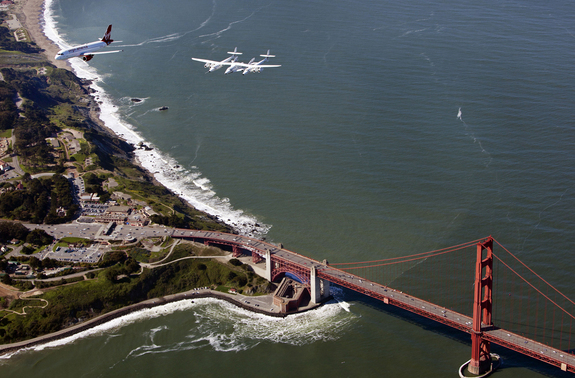 "Virgin Galactic's private SpaceShipTwo spacecraft and its mothership WhiteKnightTwo flies over the Golden Gate Bridge with the Virgin America plane ""My Other Ride is a Spaceship"" on April 6, 2011 en route to open Terminal 2 at San Francisco International Airport."