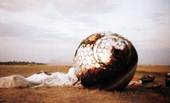 Here the re-entry capsule of the Vostok 3KA-3 (also known as Vostok 1) spacecraft (Vostok 1) is seen with charring and its parachute on the ground after landing south west of Engels, in the Saratov region of southern Russia.