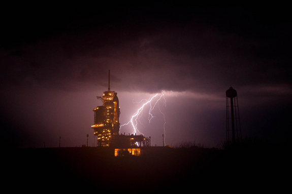 Lightning and the space shuttle Endeavour are seen at Launch Pad 39A as a storm passes by prior to the rollback of the Rotating Service Structure (RSS), Thursday, April 28, 2011, at Kennedy Space Center in Cape Canaveral, Fla.