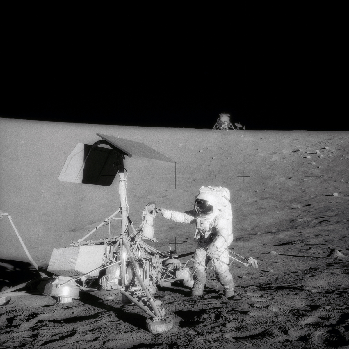 A television camera and several other pieces were taken from Surveyor 3 and brought back to Earth for scientific examination. Here, Apollo 12 moonwalker, Pete Conrad, examines the Surveyor's TV camera before detaching the gear.