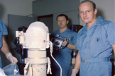 The Surveyor 3 camera shown with astronaut Pete Conrad and technicians at the NASA Lunar Receiving Laboratory upon its receipt after the Apollo 12 mission Nov. 1969. The camera was then bagged for later studies, including the microbial sampling of the camera.