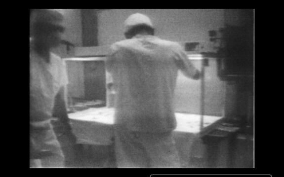 A still image taken from a digitally transcribed version of the original 16mm film of the microbial sampling of the camera. Two investigators stand in front of the laminar flow bench in which the camera resided during sampling. Note that they are wearing masks and head coverings that do not fully cover their heads, short-sleeve scrubs that do not extend below the level of the bench-top (allowing air potentially to blow into and out of them), and gloves over their hands but with no protection for their arms.
