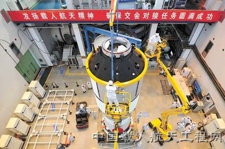 "Work is underway in readying China's thrust into a space station era with Tiangong-1, the first Chinese space station module.. The banner above the hardware reads: ""Carry on the spirit of human spaceflight, insure the complete success of the docking mission."""
