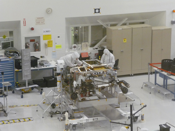 Technicians at NASA's Jet Propulsion Laboratory work on the Mars Science Laboratory rover Curiosity in May 2011. The rover is upside-down, and its six wheels are off (they rest on a table, at far right of the photo).