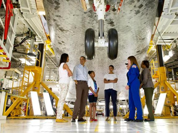 President Barack Obama, First Lady Michelle Obama, daughters Malia, left, Sasha, and Mrs. Obama's mother, Marian Robinson, walk under the landing gear of the space shuttle Atlantis. Astronaut Janet Kavandi and United Space Alliance project lead for thermal protection systems Terry White conduct the tour of Kennedy Space Center in Cape Canaveral, Fla., Friday, April 29, 2011.