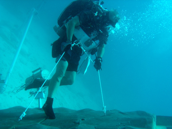 A NEEMO engineering crew diver simulates anchoring to an asteroid surface.