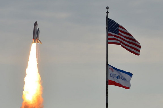 Space shuttle Endeavour appears to fly past flags in the foreground, on its way to the International Space Station. Launch of the STS-134 mission took place at 8:56 a.m. EDT on May 16.