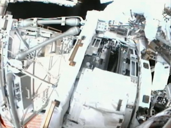 This view from a spacewalker helmet camera shows the International Space Station's port side Solar Alpha Rotary Joint (gear in center), a huge gear that turns the station's port solar arrays, during a May 22, 2011 spacewalk by astronauts Andrew Feustel and Mike Fincke.