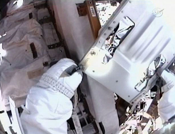This still from a video taken by the spacesuit helmet camera of astronaut Mike Fincke shows one of four loose bolts he caught as they floated free of the International Space Station during a May 22, 2011 spacewalk to grease up a solar array gear.