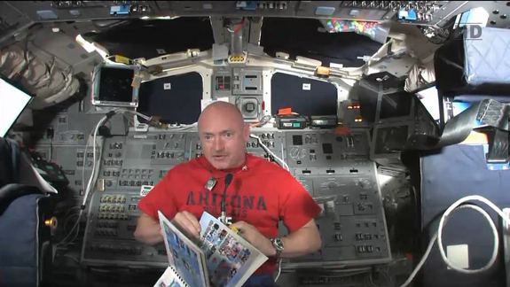 Endeavour shuttle commander and veteran astronaut Mark kelly displays the 2010-2011 yearbook of Mesa Verde Elementary School in Tucson, Ariz., which he carried to space with him on Endeavour's final spaceflight in May 2011. This still was taken from a May 22 broadcast.