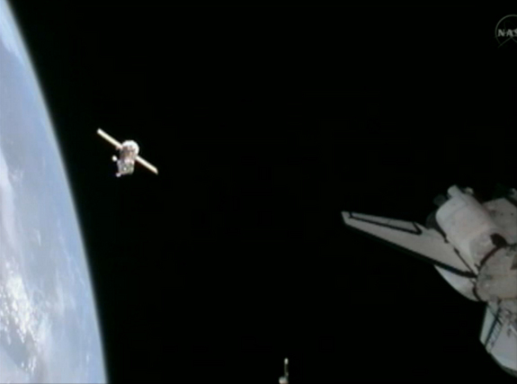 This still from NASA TV shows the Russian Soyuz TMA-20 spacecraft (left) as it backs away from the International Space Station. The shuttle Endeavour's aft section is visible at right.