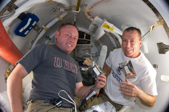 A short time before they donned spacesuits for a spacewalk, NASA astronauts Michael Fincke (left) and Andrew Feustel, both STS-134 mission specialists, are seen eating breakfast snacks onboard the International Space Station (ISS) on May 22, 2011 during Flight Day 7 of their 16-day mission.